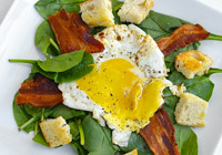 Spinach salad with fried egg and bacon