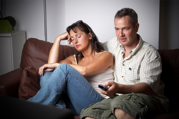 Woman bored watching tv with husband
