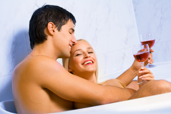 couple in bath tub with wine glasses