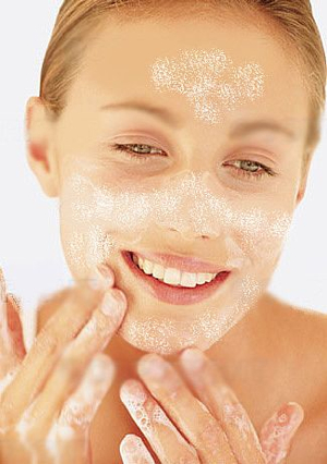 woman using cleanser on her face