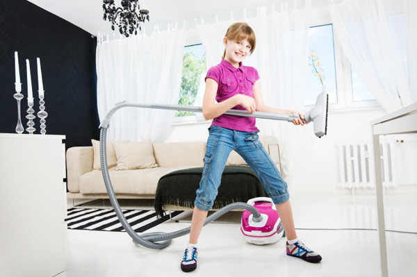 Tween girl vacuuming