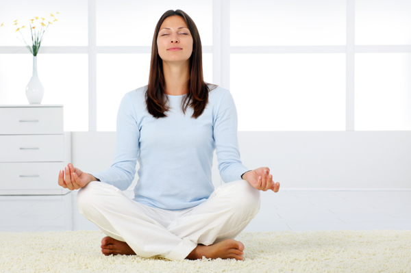 Woman meditating in living room