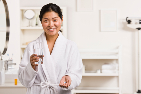 Woman taking medicine in bathroom