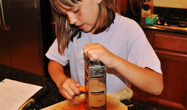 tween kid child grating carrot