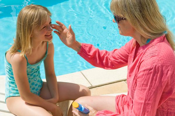 Woman applying sunscreen to child