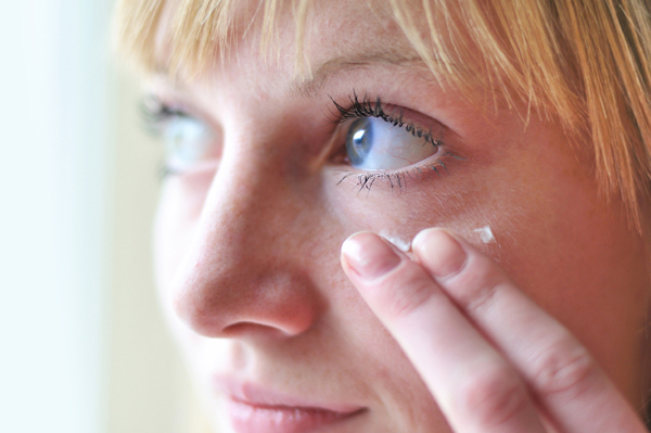 Woman applying under eye cream to hide dark circles