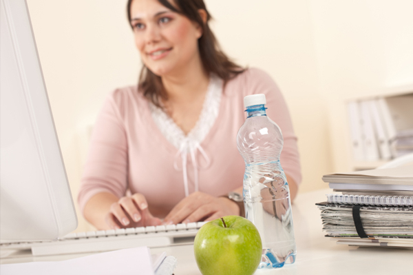 Woman with water and apple at work