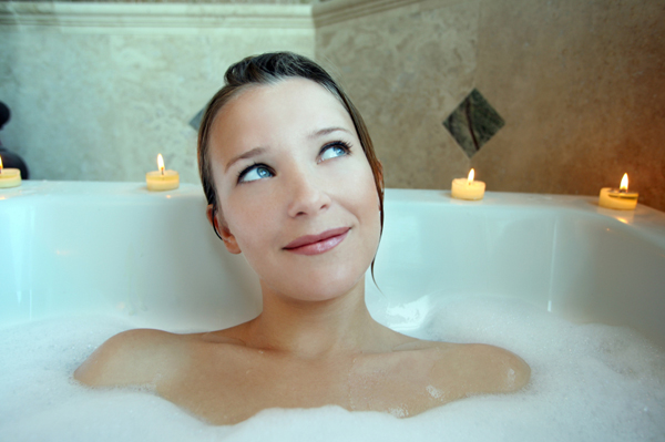 Woman in tub in redecorated bathroom