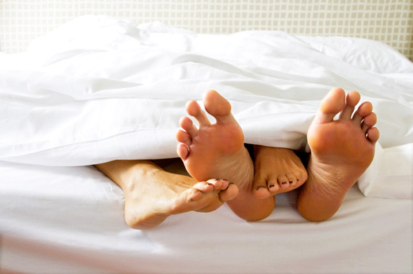 couples feet in bed