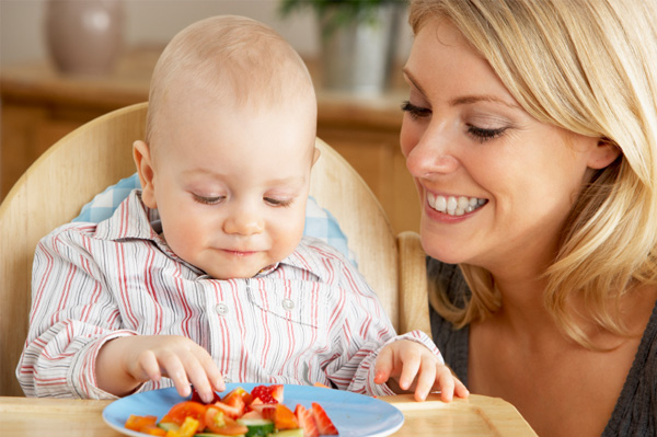 baby in high chair eating finger foods