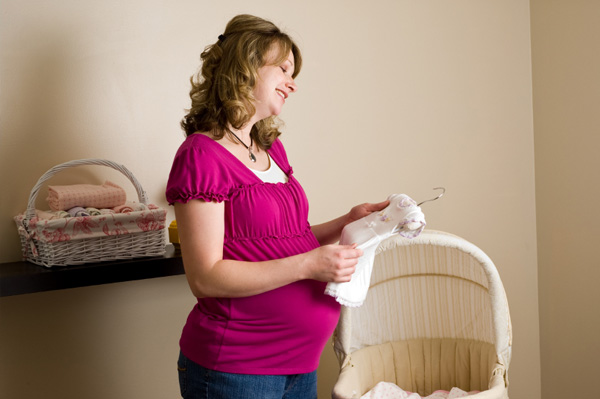Expectant mom looking at baby clothes in nursery