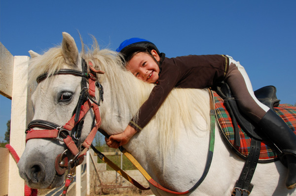 Little girl riding horse