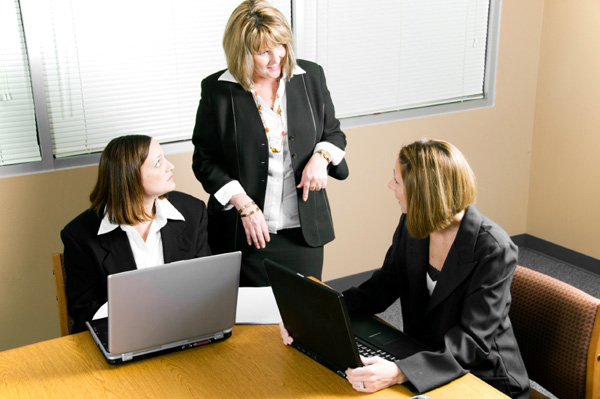 Woman delegating tasks to office workers