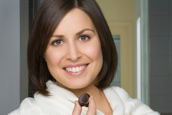 Woman eating dark chocolate heart