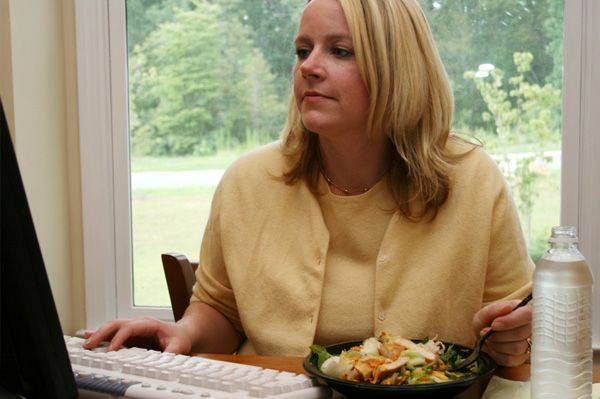 Woman eating homemade salad at work