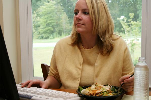 Woman eating homemade salad at work