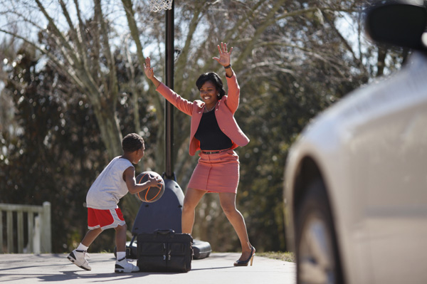 Woman playing basketball with son