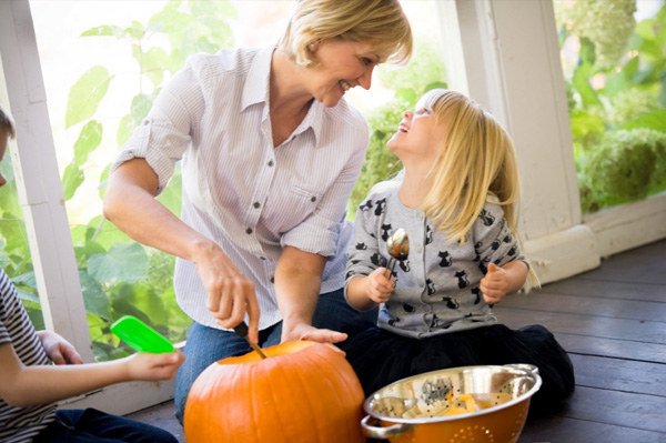 Woman carving pumpkins with kids