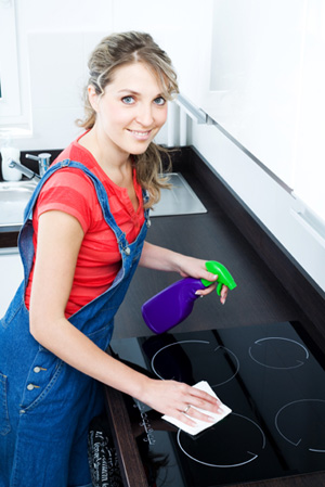 Woman cleaning glass stovetop