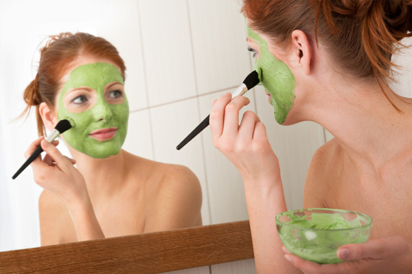 Woman putting on green mask