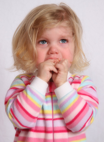 Little girl covering mouth