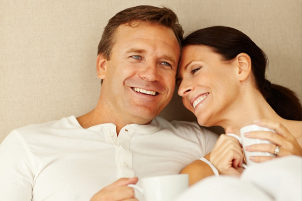 Couple in bed drinking coffee
