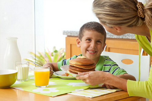 Woman serving pancakes to son