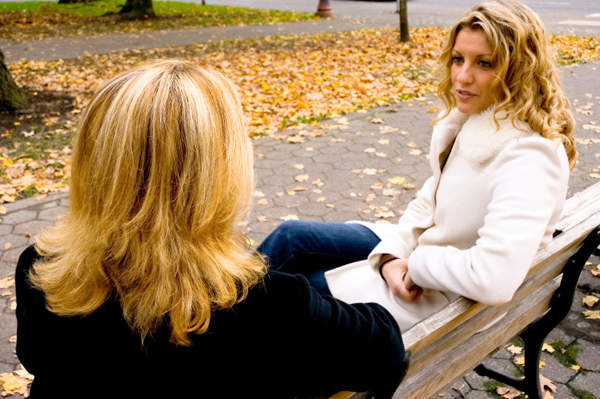Two woman talking on a bench.