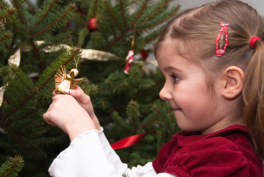 Young girl decorating a Christams tree
