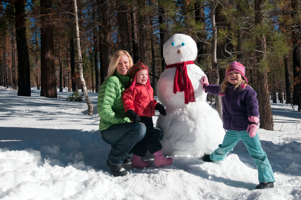 Mom building a snowman with kids