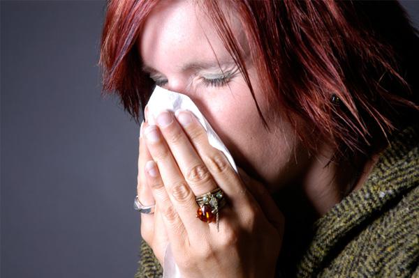 Woman in winter sneezing