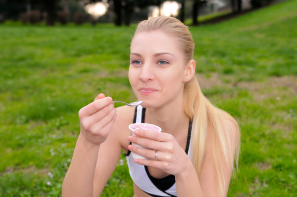 Fit woman eating yogurt
