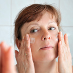 Woman putting on anti-aging moisturizer