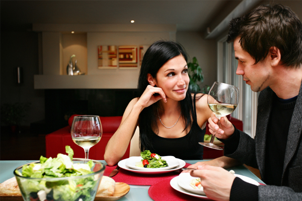 Happy couple having dinner at home