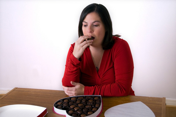 Sad woman eating chocolate
