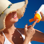 Woman putting on sunscreen