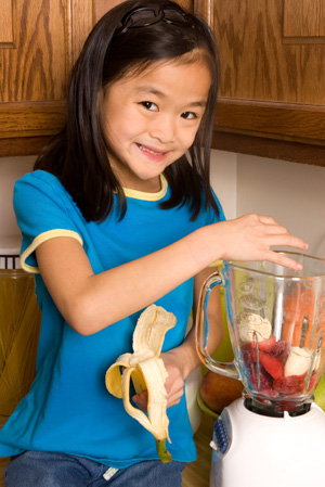 Little girl making smoothies