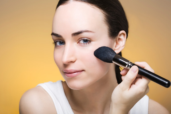Woman applying powder foundation makeup