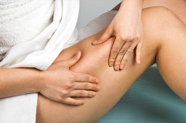 Woman inspecting cellulite on thigh
