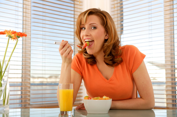 Woman eating fruit salad with yogurt