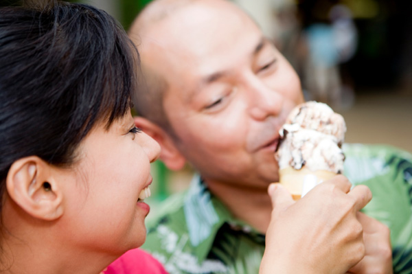 Couple sharing ice cream cone without the kids