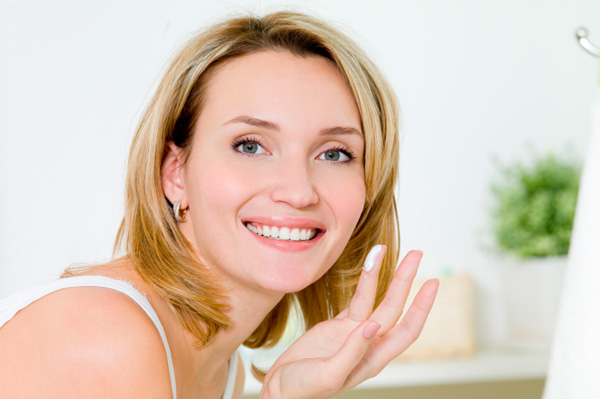 Woman applying organic face cream