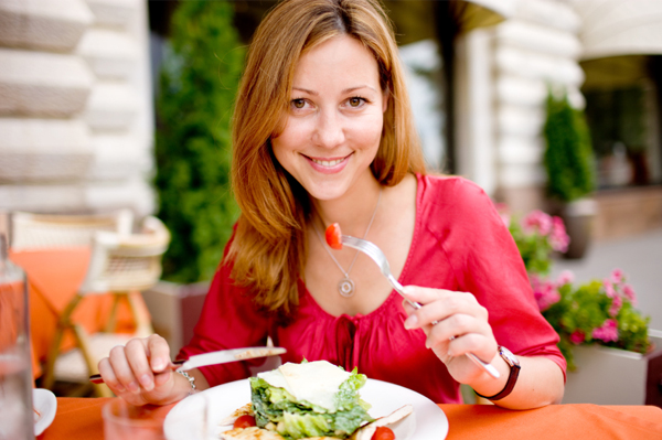 Woman eating salad at cafe