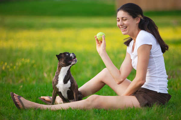 Woman playing ball with dog