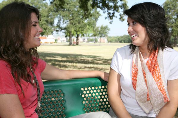 Women friends talking on park bench