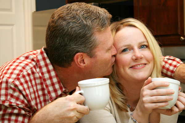 Couple kissing over coffee