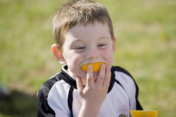 Athlete child eating orange
