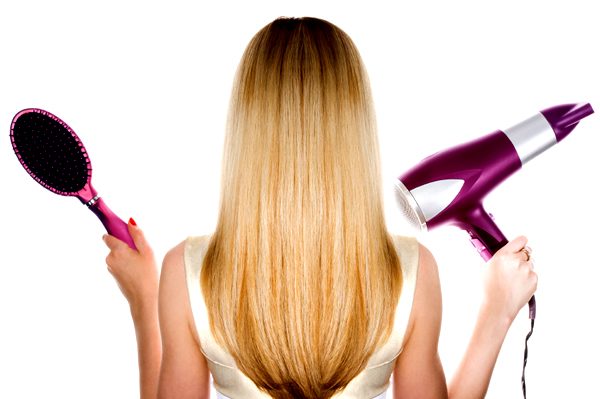 Blonde woman holding brush and hair dryer