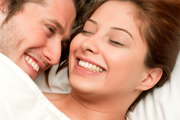 Couple smiling in bed