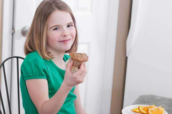 Girl eating pumpkin spice muffin